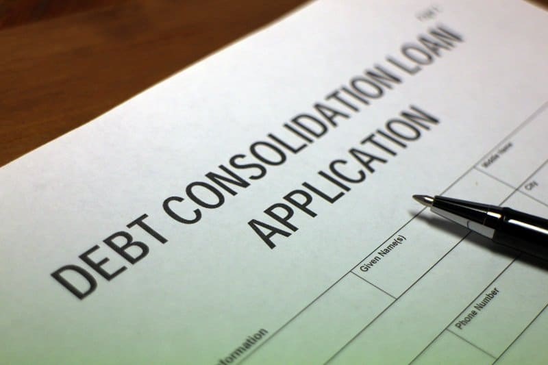Someone filling out Debt Consolidation Loan Application Form.