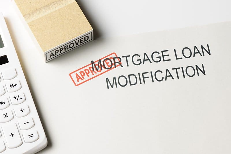 "Close-up of mortgage modification with ""Approved "" rubber stamp with calculator."